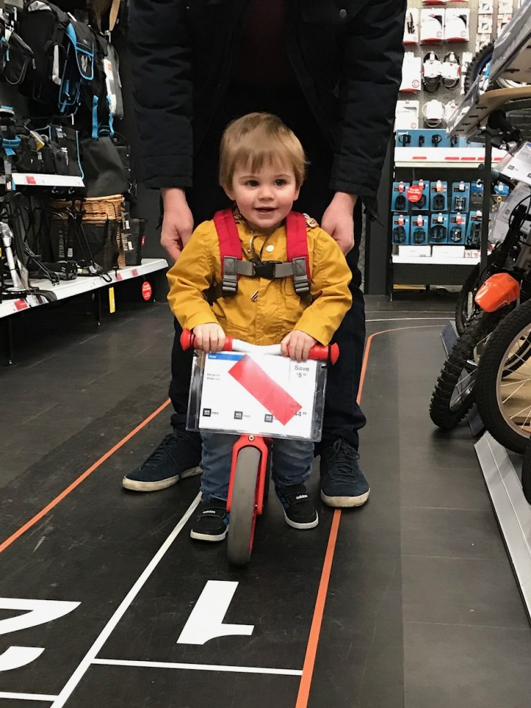 toddler riding balance bike in shop