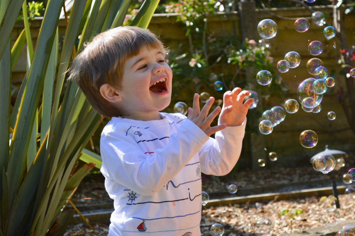 toddler playing in the garden with bubbles