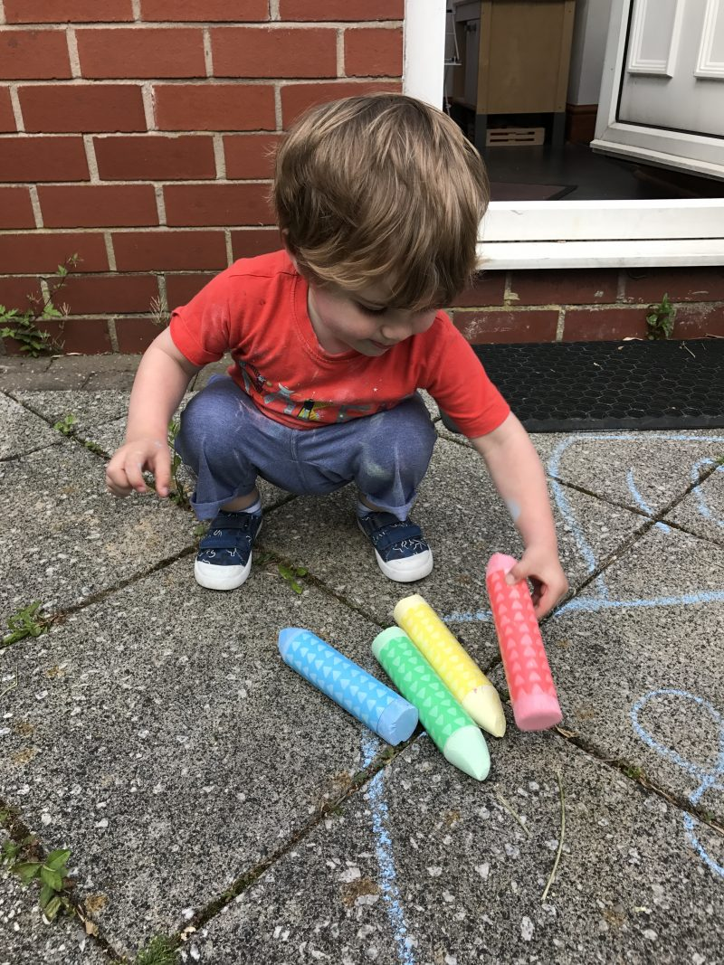 toddler playing with giant chalk