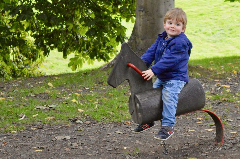 Toddler riding a horse at Nostell Priory's playground.